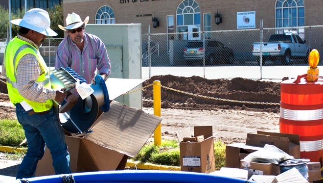 Garrett Western Construction owner Kerry Garrett, right, and employee Keelo Rivera work on the construction of the Downtown Civic Plaza on Monday.