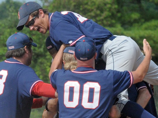 Tom Sawyer jumps on his teammates as Sister Bay celebrated its title-clinching victory over Kolberg Sunday. The Bays captured their first Door County League baseball championship in 20 years.