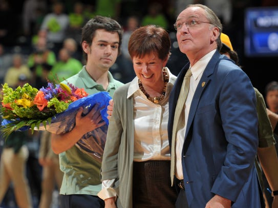 Notre Dame head coach Muffet McGraw stands with Notre Dame Athletic Director Jack Swarbrick, right, and her son, Murphy McGraw, left, as she is honored at the Purcell Pavilion on Nov. 17, 2011. McGraw was named to the Women's Basketball Hall of Fame.