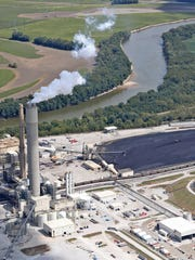 A coal ash pit can be seen to the right of Duke's Cayuga Generating Station along the Wabash river, Thursday, Sept. 7, 2017. According to a recent report from the Environmental Integrity Project, this station is one of 15 coal-fired power plants in Indiana that are leaking toxic metals into groundwater.