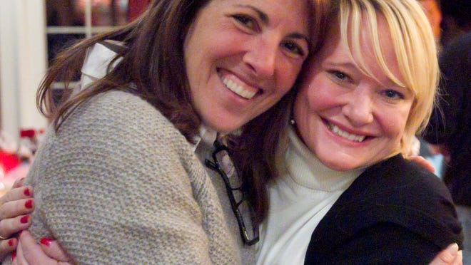 District Judge Theresa Brennan hugs friend Bridget Passeri as friends and supporters surround her to watch the results of the election come in Tuesday.