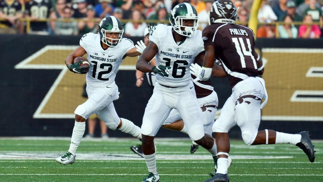 Spartans FB RJ Shelton rushes for positive yards against Bronco defenders.