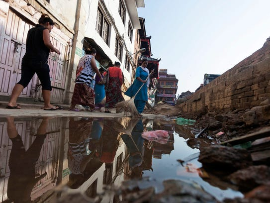 Workers clean a road near a damaged temple in Basantapur