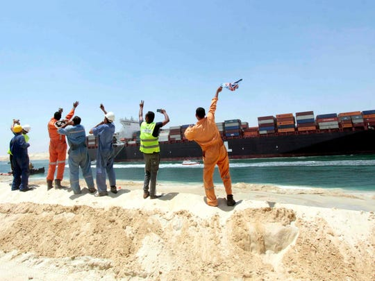 Egytpian workers wave towards a container ship sailing