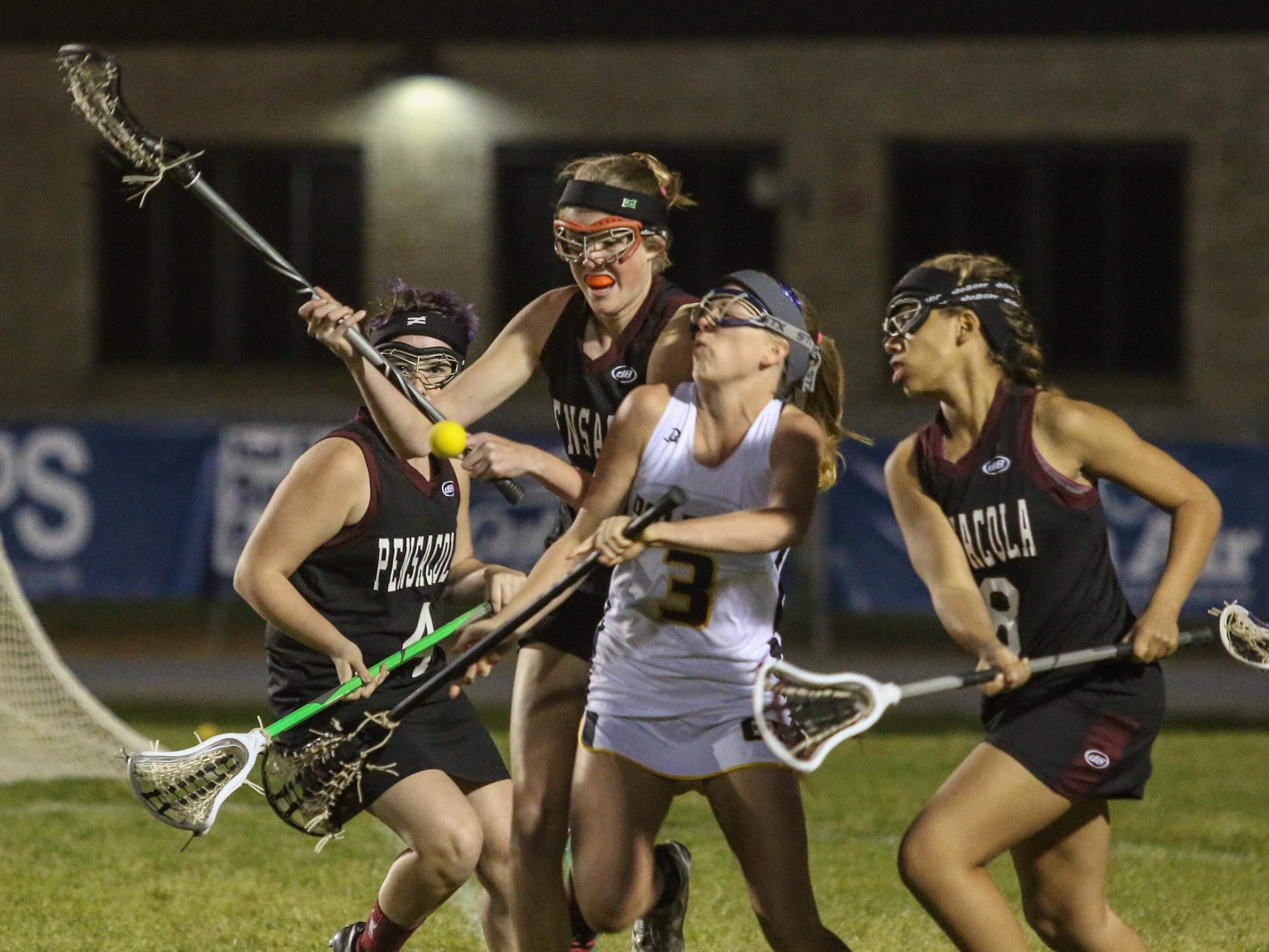 Gulf Breeze's Kaytlyn Carlson (3) gets hits from behind while trying to go between Pensacola's Roseanna Reber (4), Lillian Wiggins (27) and Kaitlyn Ham (18) Thursday night during the District 1-1A girls lacrosse championship game at Gulf Breeze High School.