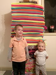 Shaynee Traska's hometown is supporting her Iditarod run. Here, Jericho Barz, 4, and his sister, Addilyn Barz, 2, of Gladwin show the stack of 36 fleece blankets they  helped to make for Traska's dogsled team to ensure the dogs stayed warm.
