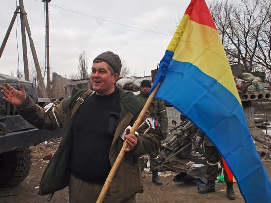 A pro-Russia rebel holds a flag of the rebel-held city