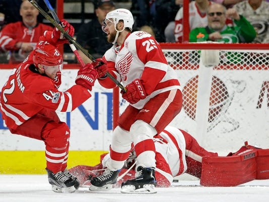 Carolina Hurricanes' Joakim Nordstrom (42), of Sweden, scores against Detroit Red Wings goalie Jimmy Howard as Red Wings' Mike Green (25) defends during the first period of an NHL hockey game in Raleigh, N.C., Tuesday, March 28, 2017. (AP Photo/Gerry Broome)