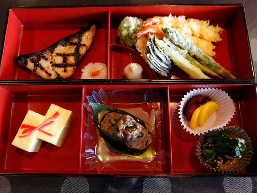 A bento box from Ando Japanese Restaurant and Sushi Bar, in Blue Ash, featuring gindara (grilled black cod marinated in meso sauce), tempura (a variety of vegetables and three pieces of fried shrimp), tomago (sushi omelet), gyu maki (asparagus wrapped in beef loin), oshinko (Japanese pickles) and goma-ae (spinach with sweet sesame dressing.
