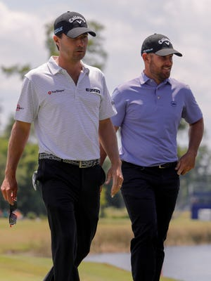 Kevin Kisner and Scott Brown leave the ninth green after completing their round Friday.