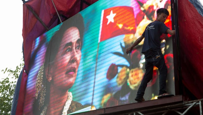 A volunteer covers a large-screen TV showing images of Aung San Suu Kyi during a rainstorm at the opposition party headquarters in Yangon, Myanmar, Monday, Nov. 9, 2015.