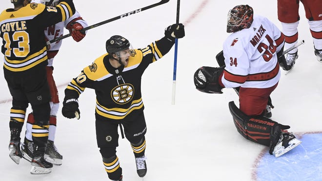 Boston Bruins left wing Anders Bjork (10) celebrates a goal, scored by teammate Charlie Coyle (13), in front of Carolina Hurricanes goaltender Petr Mrazek (34) during the second period of an Eastern Conference Stanley Cup playoff game, Wednesday, in Toronto.