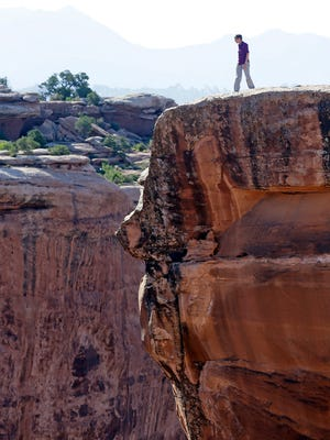 "This July 14, 2016, file photo, U.S. Interior Secretary Sally Jewell looks in to a canyon at Gemini Bridges near Moab, Utah, during a tour to meet with proponents and opponents to the ""Bears Ears"" monument proposal. President Barack Obama designated two national monuments Wednesday, Dec. 28, at sites in Utah and Nevada that have become key flashpoints over use of public land in the U.S. West. (AP Photo/Rick Bowmer, File)"