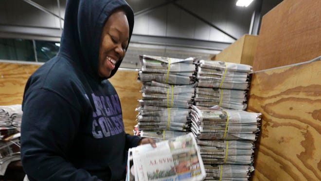 Lateshia Duke packages bundles of newspapers to be delivered to commercial outlets in 2017 as the Thanksgiving Day Milwaukee Journal Sentinel completes the press run.