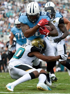 Titans running back Derrick Henry (22) powers over a Jaguars defender for a third-quarter touchdown at EverBank Field on  Sunday, Sept. 17, 2017.