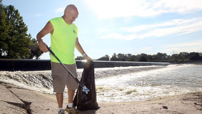 Hamilton resident Steve Monnin, 57, picks up trash near the spillway at James G. Combs Memorial Park in Hamilton. He was fed up with the condition of the park and began cleaning it up himself.
