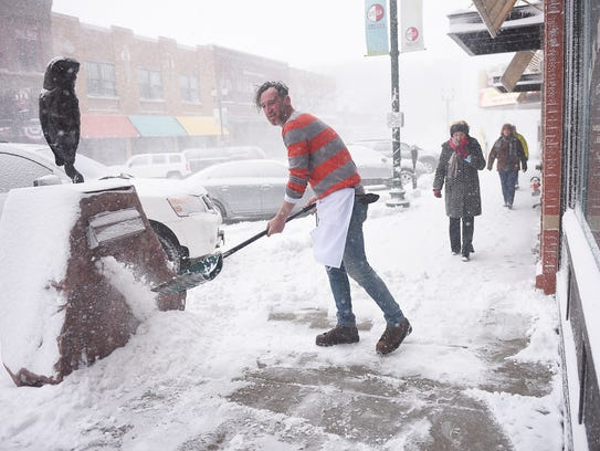 M.B. Haskett cook Mark Romanowski shovels snow in front