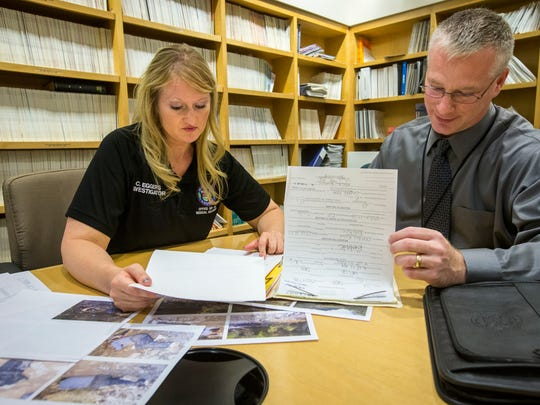 Medicolegal death investigator Christen Eggers (left) and Detective Stuart Somershoe go over records of a middle-aged male who died of natural causes at Piestewa Peak in Phoenix in May 2003.