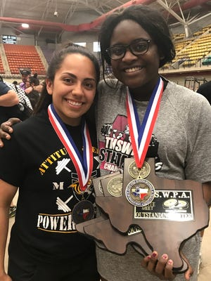 Snyder powerlifters Cheyenne Avila, left, and Kerrington Biggers show off their hardware from the Texas High School Women's Power Association 2018 State Championships on Saturday in Waco.