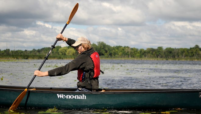 Conservation Corps Minnesota crew member Cody Mastel canoes during an I Can Paddle! class in July 2014 at Lake Maria State Park near Monticello.