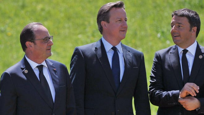 French President Francois Hollande, left, Britain's Prime Minister David Cameron, center, and Italy's Prime Minister Matteo Renzi chat after posing for a picture at the Elmau Castle resort near Garmisch-Partenkirchen on June 7, 2015.