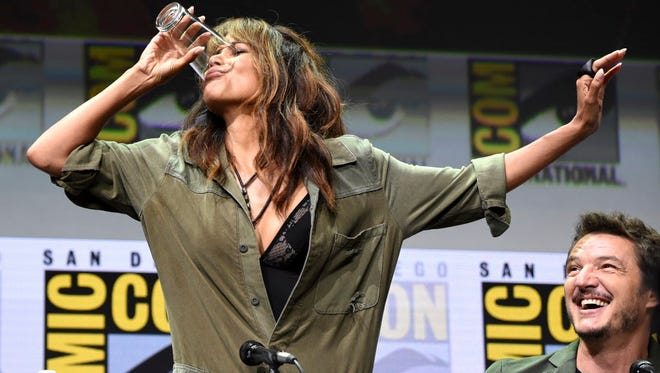 Halle Berry downs a full glass of bourbon as Pedro Pascal looks on at 20th Century Fox's 'Kingsman: The Golden Circle' panel on Thursday at Comic-Con.