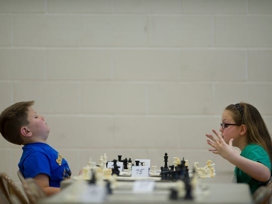 Scott Elementary School student Wesley Roeder, 9, left, eeks out a win over Mount Vernon Elementary School's Faith Mattingly, 8, at the North Junior High School Spring Scholastic Chess Tournament Saturday morning.