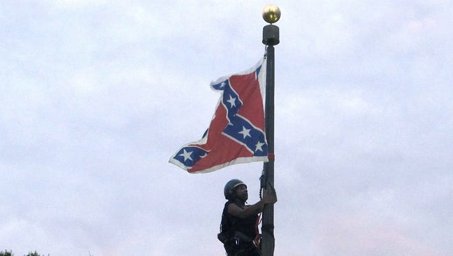 Bree Newsome of Charlotte, N.C., climbs a flagpole to remove the Confederate battle flag at a Confederate monument in front of the Statehouse in Columbia, S.C., on Saturday. She was taken into custody when she came down. The flag was raised again by capitol workers about 45 minutes later.