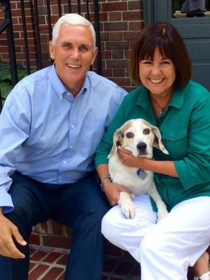 Gov. Mike Pence and First Lady Karen Pence pose with their family dog, Maverick.