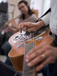 Dave Thier leads a group of musicians in a bluegrass