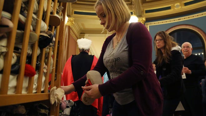 Abby Maas, of Pella adds a pair of baby shoes to the display representing the lives lost to abortion in Iowa during the pro-life Rally for Life on Thursday, March 30, 2017, at the Iowa Capitol.