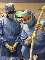 Prosper Tarley '18, a St. George's nedical assisting student learns about surgically realigning a femur from a doctor at A.I. duPont Hospital for Children.