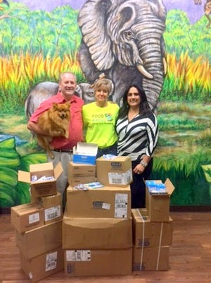 Dr. Kenneth Childress and his wife, Laura, deliver dental supplies to Elizabeth Potter, center, to be added to food-filled backpacks distributed to Lincoln County students who sign up for the program.