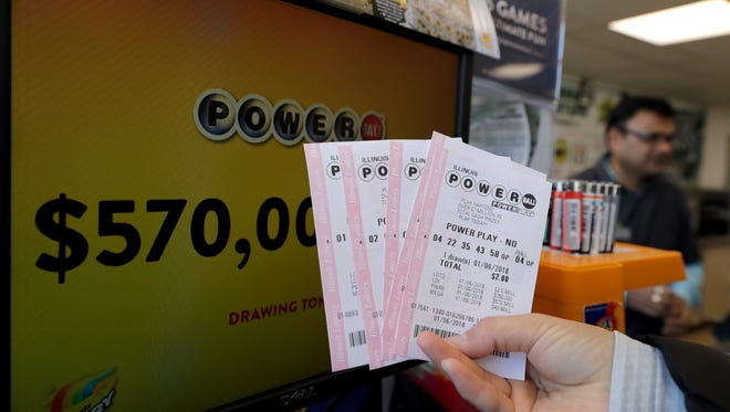 A customer shows her purchased Powerball tickets at a convenience store Saturday, Jan. 6, 2018, in Chicago.