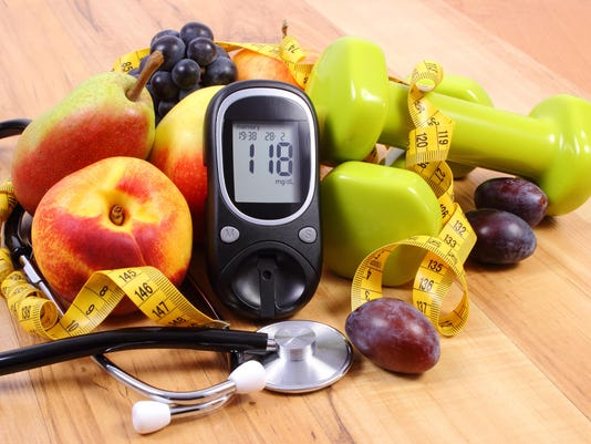 Glucose meter with medical stethoscope, fruits and dumbbells