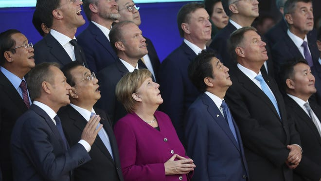 European Union and Asian leaders look up at a drone during a group photo during an EU-ASEM summit in Brussels, Oct. 19, 2018. EU leaders met with their Asian counterparts Friday to discuss trade, among other issues.