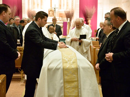 A cross is placed on the casket containing the remains