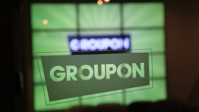 In this Sept. 22, 2011 file photo, the Groupon logo etched in glass is shown in the lobby of the online coupon company's Chicago offices.