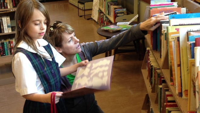 Paulina Rivet, 8, and her mom, Sara, look through the children's books at the Delta Township District Library's used book store.