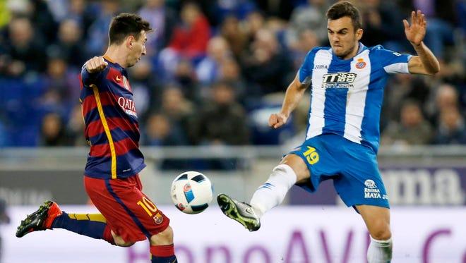 El delantero argentino del F. C. Barcelona, Leo Messi (i), se dispone a golpear el balón ante el centrocampista del Espanyol, Joan Jordán.