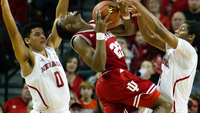 Dec 31, 2014; Lincoln, NE, USA; Indiana Hoosiers guard Stanford Robinson (22) drives against Nebraska Cornhuskers guard Tai Webster (0) and guard/forward Shavon Shields (31) at Pinnacle Bank Arena. Mandatory Credit: Steven Branscombe-USA TODAY Sports