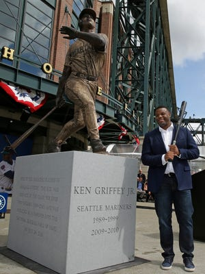 Seattle Mariners Hall of Famer Ken Griffey Jr. poses for a photo with a statue of him that was unveiled April 13, 2017, in front of Safeco Field.
