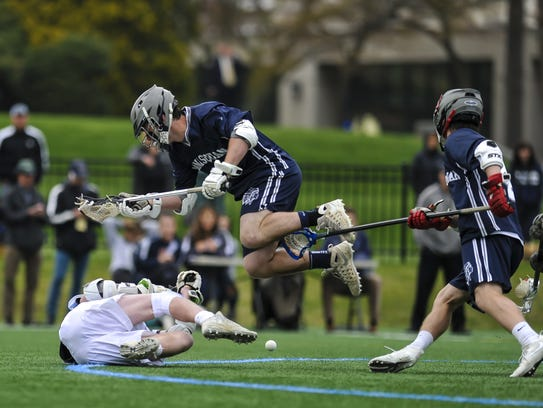 Evan Hilla of Manasquan, center, collides with Nick