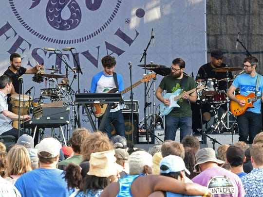 Snarky Puppy band leader Michael League, center, performs