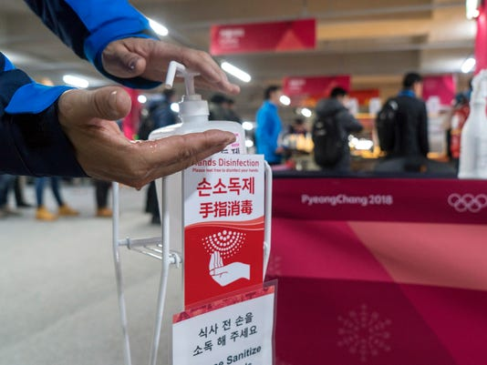 A man sanitizes his hands at the entrance to the media cafeteria in Gangneung, South Korea, Wednesday, Feb. 7, 2018. South Korean authorities deployed 900 military personnel at the Pyeongchang Olympics on Tuesday after the security force was depleted by an outbreak of norovirus. (Paul Chiasson/The Canadian Press via AP)