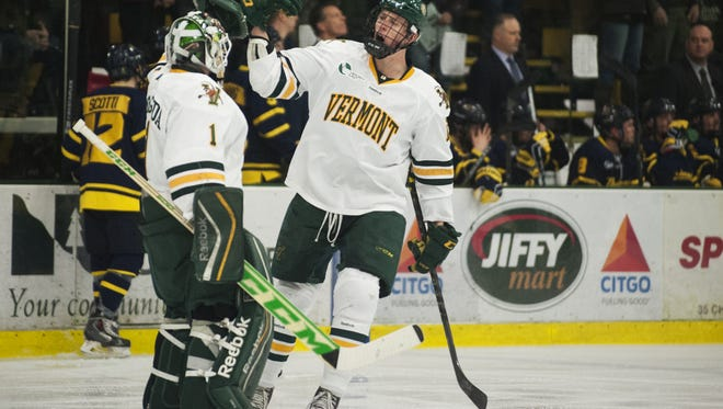 Catamounts defenseman Dan Senkbeil (13) celebrates a goal with Catamounts goalie Mike Santaguida (1) during the men's hockey game between the Merrimack Warriors and the Vermont Catamounts at Gutterson Field House on Friday night February 20, 2015 in Burlington, Vermont. (BRIAN JENKINS, for the Free Press)