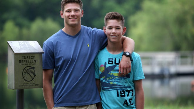 Isaiah (left) and Jaden Feterl stand next to Isiah's Eagle Scout project at the Outdoor Campus. Isaiah decided to provide bug spray to visitors after younger brother Jaden contracted the West Nile virus.