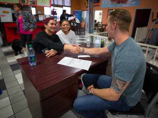 Taylor Sippy, Primetime Fitness's Membership Coordinator shakes the hand of new member Ismael Montes on Saturday morning as Sabrina Garcia looks on.