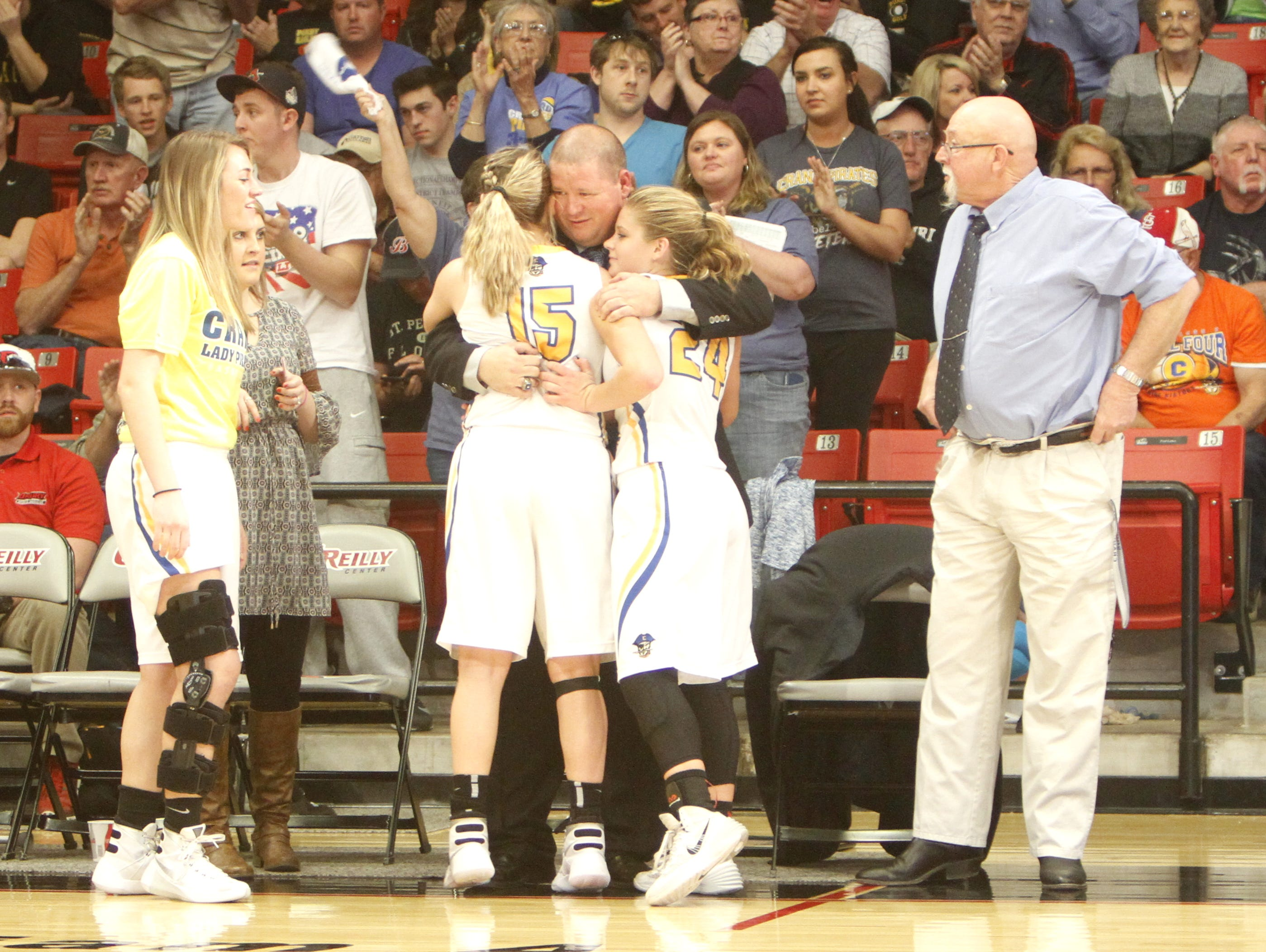 Crane girls basketball coach Jeremy Mullins (center) celebrates with seniors Justeen Mahan (15) and Kylee Moore (24) moments after Crane clinched a fourth consecutive berth in the Class 2 final four with a 64-48 win over Gainesville.