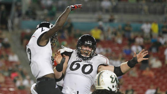 Bearcats wide receiver Mekale McKay (2) is congratulated by offensive linesman Sam Longo (60) after McKay scored a touchdown against South Florida in October of 2013.
